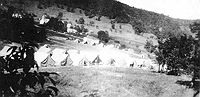Early encampment: Tent City in 1935. In the background center is the Quiet Dell School. To its left and behind is the ribbon which is State Route 20 (Clarksburg to Buckhannon route) and is now in the vicinity of Exit 115 of I-79.