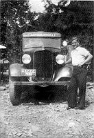 Mike Shaffer of Fairmont beside his ambulance at Camp Seebert. Mike was a jack of all trades in camp when he wasn't on call for medical emergencies.  After serving in WW ll, he woked in Marion County.