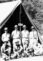 "Officers and enlisted, army leaders of Camp Wyoming. Standing, L to R are Captain Charles May, Lt C. Barrien, Captain J. West and the camp surgeon, Lt L. Zwick, MD. Kneeling/sitting, L to R are SSgt N. Capps, Sgt A. Gardner, Sgt E. Wiggins and Pvt E. Yonkowski, cook (Source: NACCCA and ""Written on the Land"")"