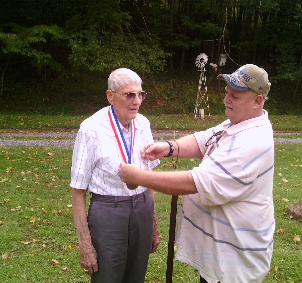 Mr. Doug Sparks, West Virginia State CCC Museum Rep, of Clarksburg places CCC Hall of Fame medallion on Mr. Teddy Davis during ceremonies in Lewis County.